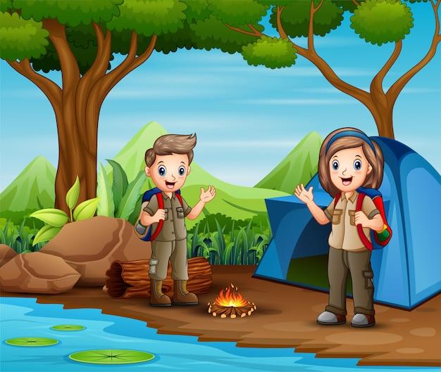 Cartoon jongen en meisje scouts op kamp Premium Vector