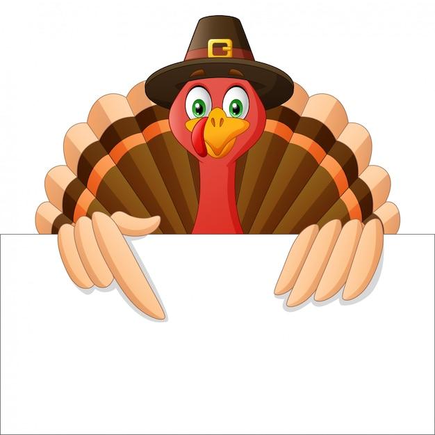Cartoon thanksgiving kalkoen vogel mascotte karakter houden een leeg bord Premium Vector
