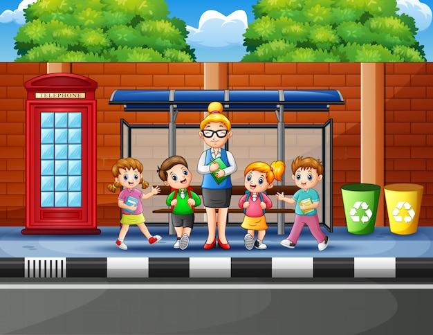 Cartoon van schoolkinderen in de bushalte met een leraar Premium Vector