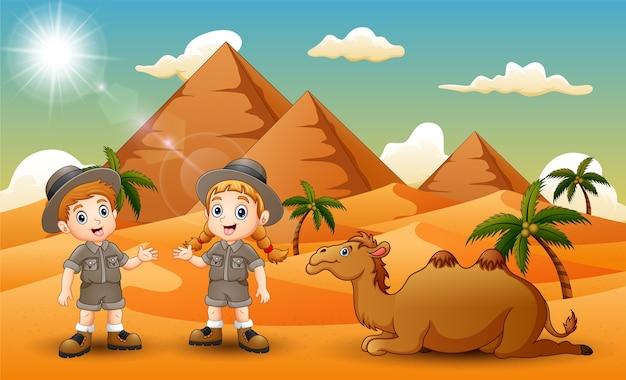 Cartoon van twee kinderen die een kameel in de woestijn hoeden Premium Vector