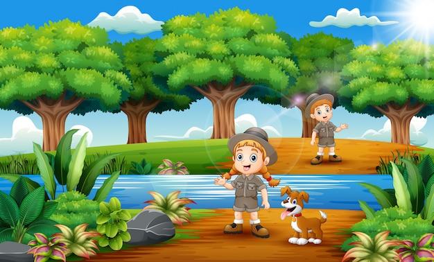 Cartoon van zookeeper jongen en meisje met hond in de jungle Premium Vector