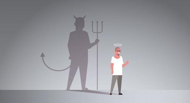 Casual man met nimbus kiezen tussen goede en kwade schaduw van de duivel Premium Vector