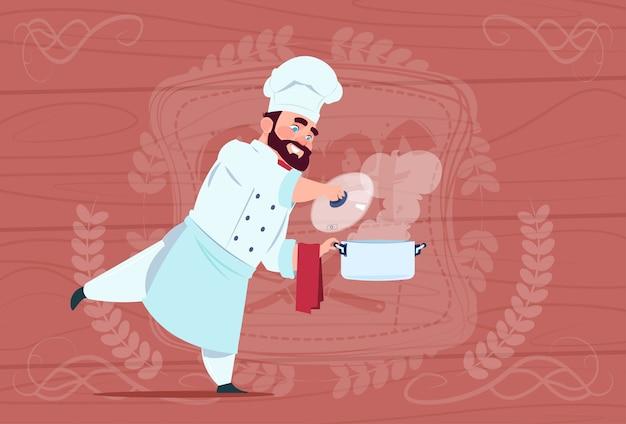Chef-kok cook holding steelpan met warme soep lachende cartoon chief in white restaurant uniform over houten getextureerde achtergrond Premium Vector