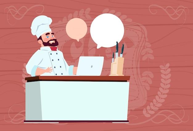 Chef-kok cook werken op laptop computer cartoon restaurant chief in witte uniform zit aan bureau over houten gestructureerde achtergrond Premium Vector