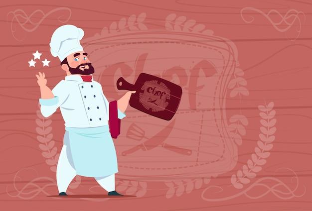 Chef-kok hold board lachende cartoon restaurant chief in white uniform over houten getextureerde achtergrond Premium Vector