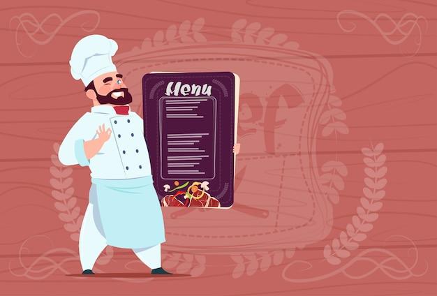 Chef-kok holding restaurant menu lachende cartoon chef in white uniform over houten gestructureerde achtergrond Premium Vector