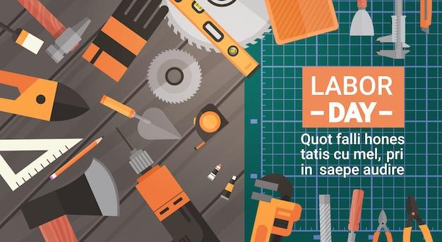 Dag van de arbeid wenskaart over set van hulpmiddelen voor reparatie en bouw Premium Vector