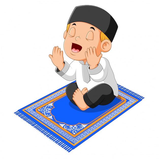 De jongen is aan het bidden en zit op het blauwe gebedskleed Premium Vector