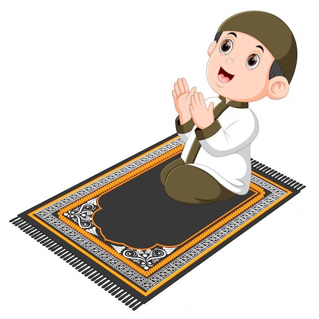De jongen met de bruine pet bidt op het bruine gebedskleed Premium Vector