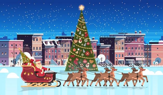 De kerstman in slee met rendieren verfraaide dichtbij sparrenstad de bouwhuizen Premium Vector