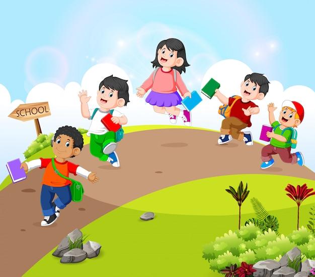 De kinderen lopen op de weg naar school gaan Premium Vector