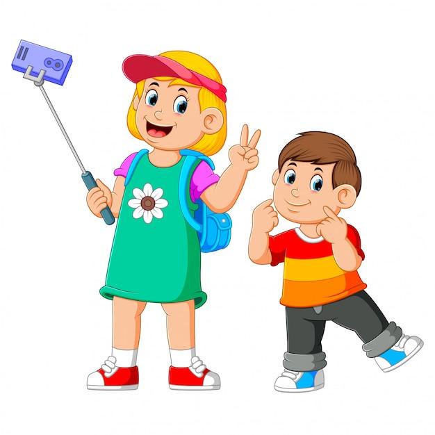 De kinderen poseren samen en nemen een selfie Premium Vector