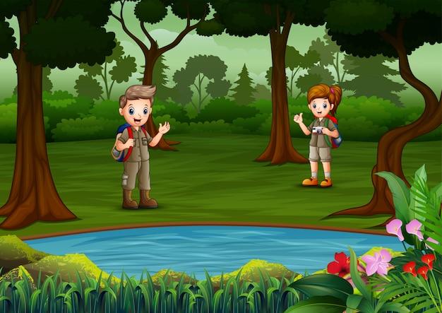 De ontdekkingsreizigerjongen en het meisje rusten bij het meer Premium Vector