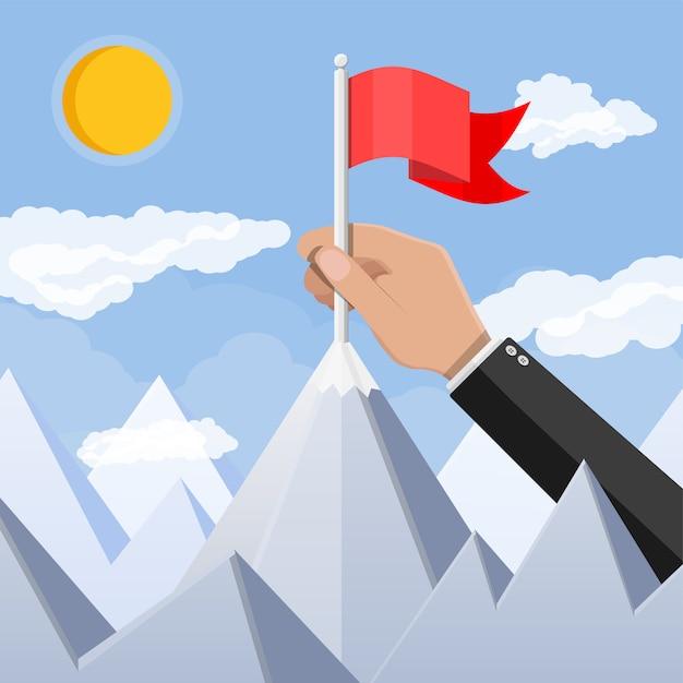 De zakenmanhand zet vlag op piek van berg. Premium Vector