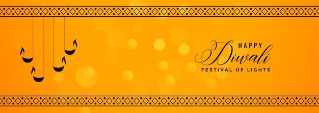 Deepawali gele banner met decoratieve diya en patroongrens Gratis Vector