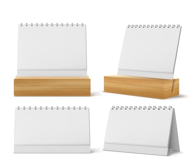 Desktopkalenders met metalen spiraal en blanco pagina's geïsoleerd op een witte achtergrond. realistisch van papieren kalender, kantoorplanner of notitieblok op tafel of houten displaystandaard Gratis Vector
