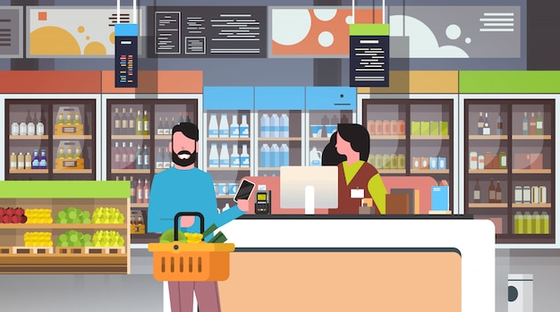 Detailhandelaar kassier bij kassa supermarkt Premium Vector
