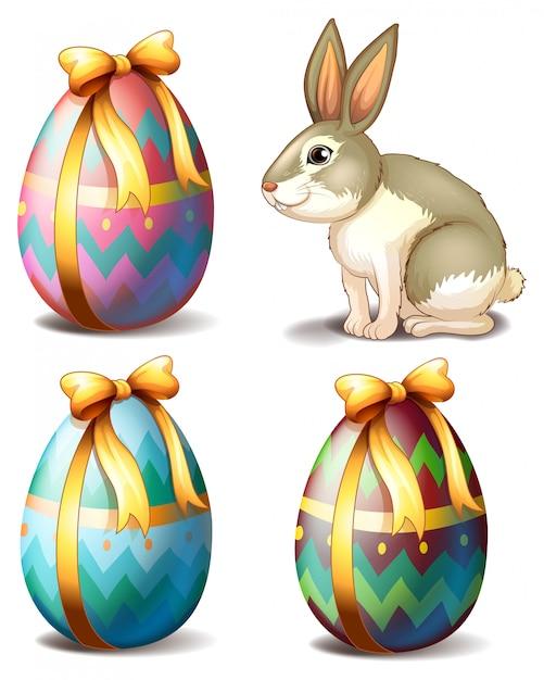 Drie kleurrijke eieren en een schattig konijntje Gratis Vector