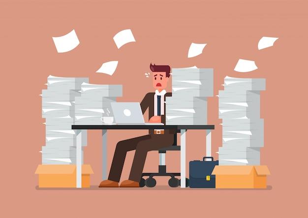 Drukke overwerkte man zit aan tafel met laptop en stapel papieren in office Premium Vector