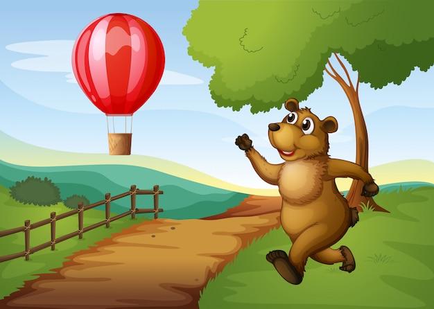 Een beer die achter de heteluchtballon aan rent Gratis Vector
