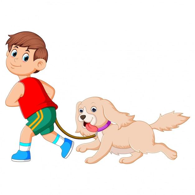Een gelukkige jongen rent en trekt aan zijn schattige bruine hond Premium Vector