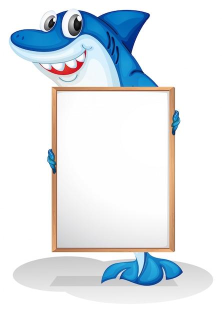 Een glimlachende haai die een leeg whiteboard houdt Gratis Vector