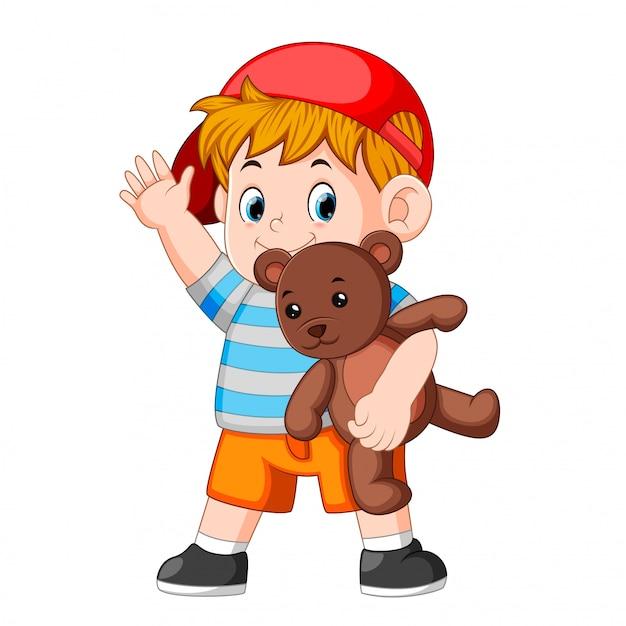 Een grappige jongen spelen met de teddybeer Premium Vector
