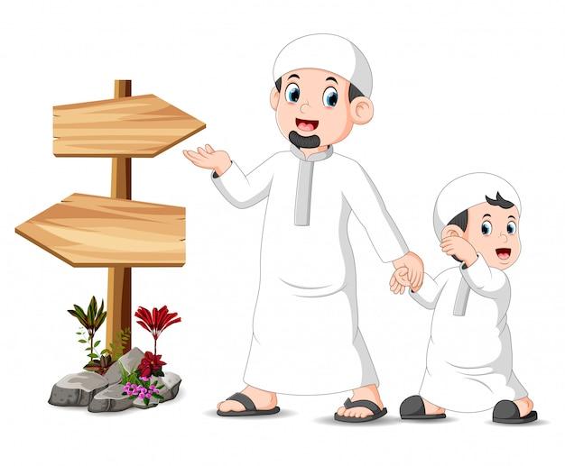 Een kind met zijn vader staat en poseert in de buurt van de lege houten wegwijzer Premium Vector