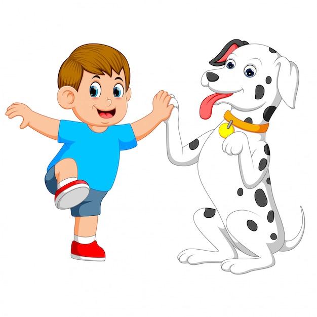 Een schattige hond speelt met zijn baasje en houdt zijn hand vast Premium Vector