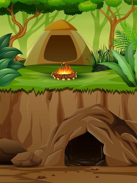 Een tent met kampvuur boven een ondergrondse grot Premium Vector