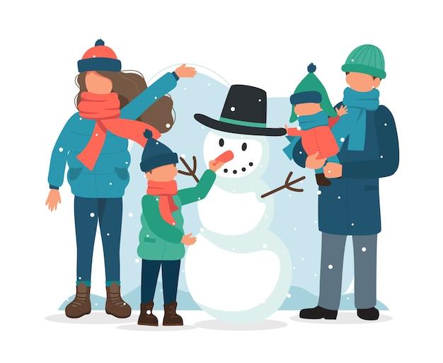 Familie die een sneeuwman in de winter maakt. Premium Vector