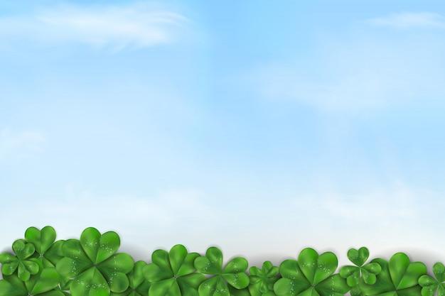 Fijne st patrick's day. st patricks dagontwerp met blauwe hemel en wolken, het blad van de klaverklaver op de achtergrond van de de lenteaard. Premium Vector