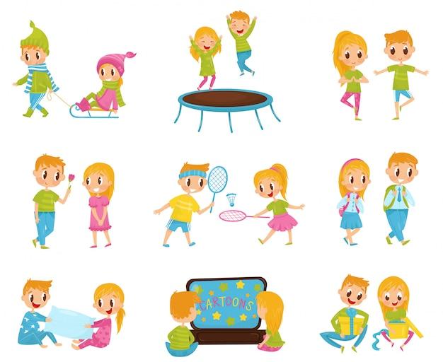 Flat set met schattige kleine jongen en meisje in verschillende acties. springen op de trampoline, tekenfilms kijken, cadeautjes openen Premium Vector