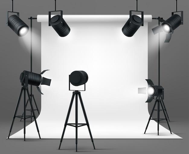 Fotostudio met schijnwerpers en witte achtergrond Gratis Vector