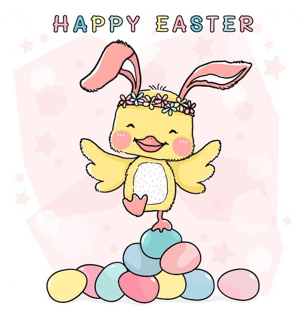 Gelukkig kleine gele kip met konijnenoren, staande op stapel kleurrijke pastel paaseieren Premium Vector
