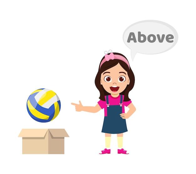 Gelukkig schattig jong geitje meisje met bal en doos, leren voorzetsel concept, boven voorzetsel en poseren geïsoleerd Premium Vector