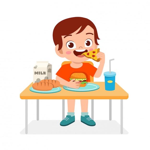 Gelukkig schattige jongen jongen eet fastfood Premium Vector