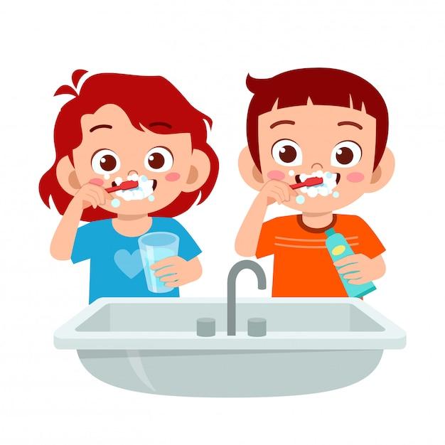 Gelukkig schattige jongen jongen en meisje poetsen schone tanden Premium Vector