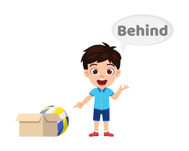 Gelukkig schattige jongen jongen met bal en karton, voorzetsel concept leren, tussen voorzetsel en wijzen geïsoleerd Premium Vector