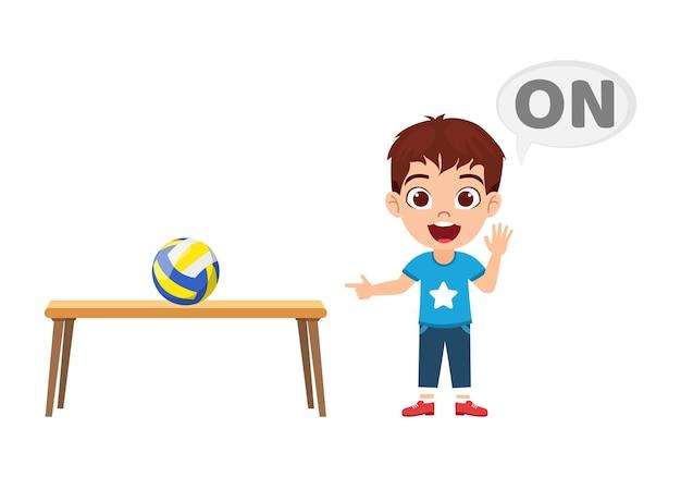 Gelukkig schattige jongen jongen met bal en tafel, voorzetsel concept leren, op voorzetsel en wijzen Premium Vector