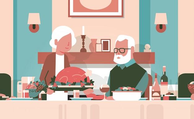 Gelukkige dankzegging bejaarde echtpaar vergadering tafel vieren bedankt dag Premium Vector