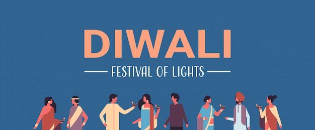 Gelukkige diwali indiase mensen groep dragen nationale traditionele kleding bedrijf olielamp banner Premium Vector