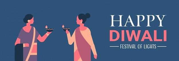 Gelukkige diwali indiase vrouwen houden olielamp kaars viering banner Premium Vector