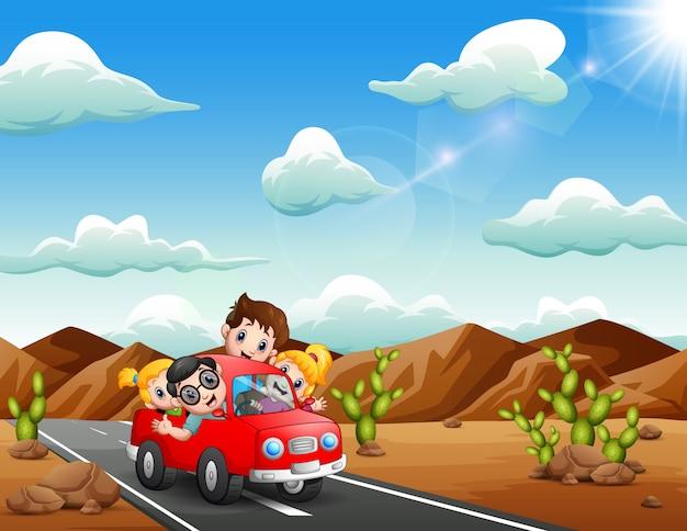 Gelukkige kinderen die door rode auto door de woestijn reizen Premium Vector