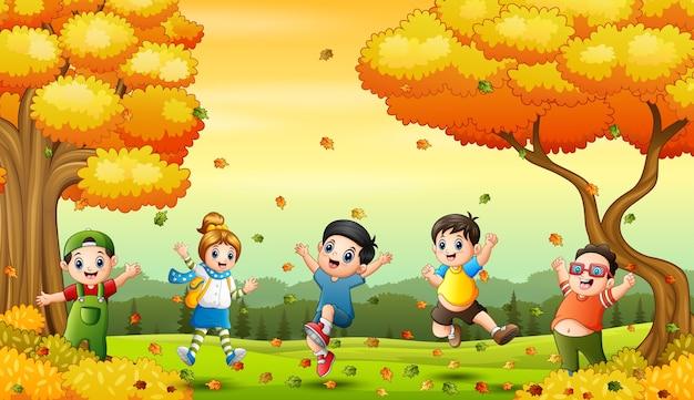 Gelukkige kinderen spelen met gevallen bladeren Premium Vector