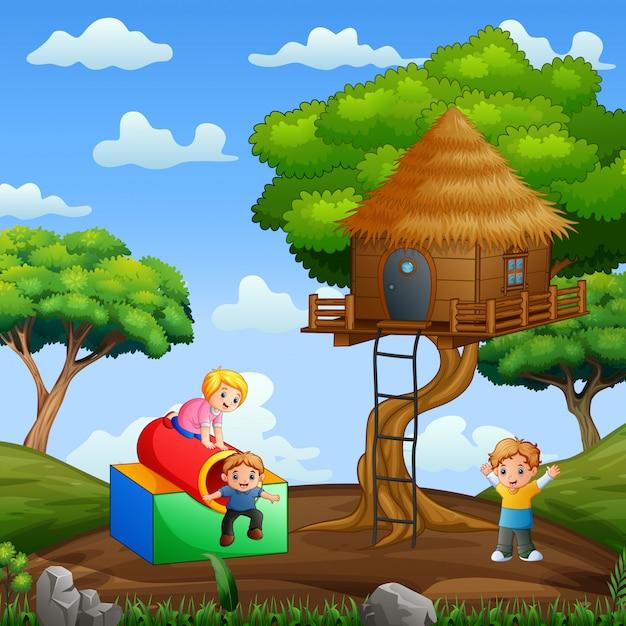 Gelukkige kinderen spelen rond boomhut 's nachts Premium Vector