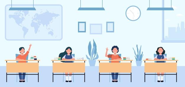 Gelukkige leerlingen studeren in de klas geïsoleerde vlakke afbeelding. kinderen stripfiguren zitten aan tafels in schoolles. Gratis Vector