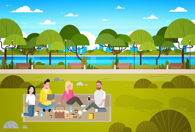 Gelukkige mensen met picknick in park groep jonge mannen en vrouwen zittend op gras ontspannen Premium Vector