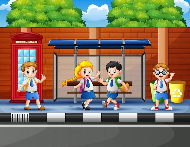 Gelukkige schoolkinderen bij de bushalte Premium Vector