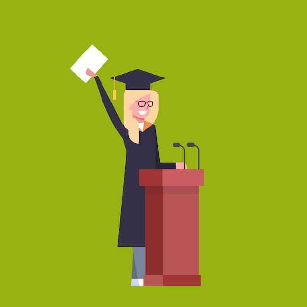 Gelukkige studente in graduatie glb en toga die zich bij het diploma van de tribunaholding bevinden Premium Vector